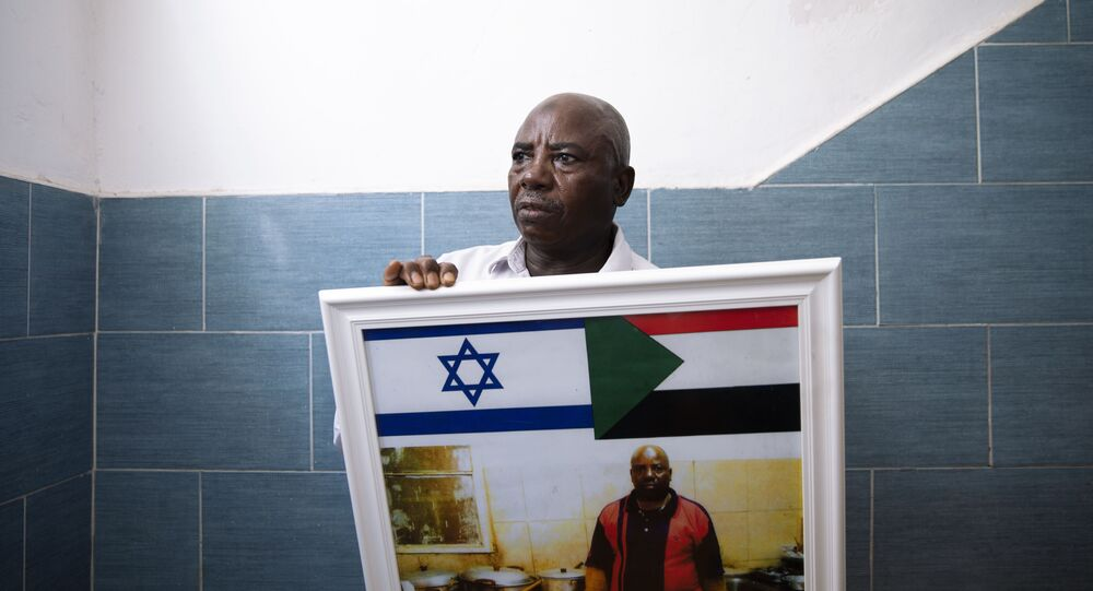 O migrante sudanês Attom Alialdom segura uma foto de seu antigo restaurante decorado com bandeiras sudanesas e israelenses, do lado de fora de sua casa no sul de Tel Aviv, Israel, domingo, 25 de outubro de 2020.