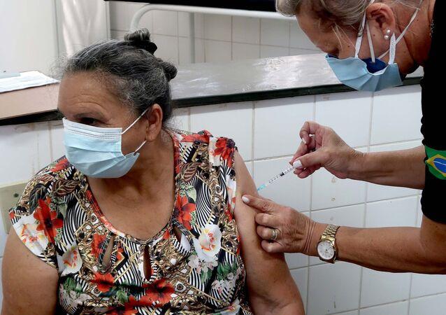 Idosa de 68 anos recebe a primeira dose da CoronaVac em Ribeirão Preto (SP), no dia 2 de abril de 2021