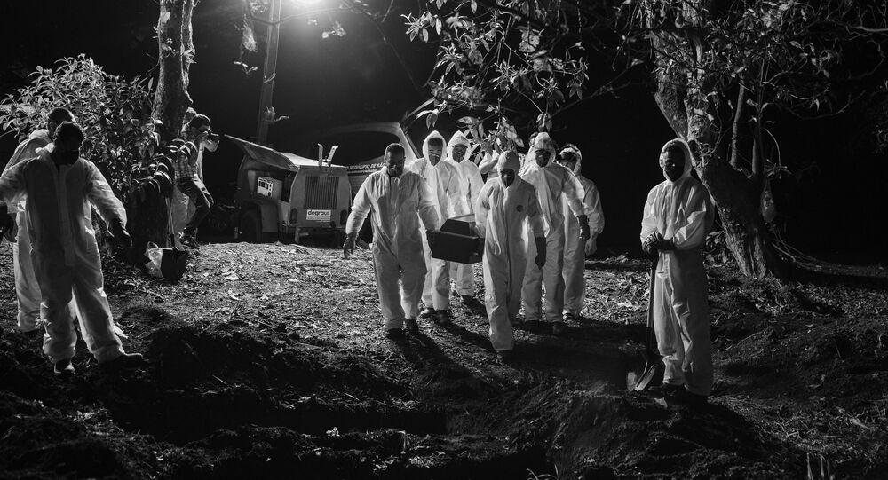 Sepultadores, usando trajes de proteção, carregam caixão com vitima da COVID-19, iluminados por holofotes no Cemitério Vila Formosa, na zona leste de São Paulo.