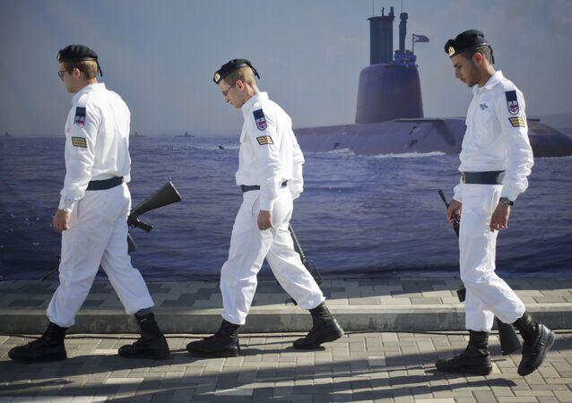 Marinheiros israelenses passam por cartaz de submarino no porto de Haifa, Israel