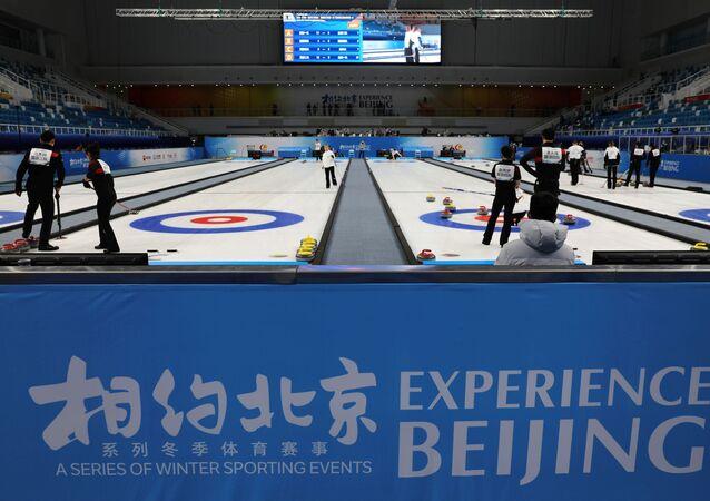 Atletas participam de competição de curling durante um evento de teste para os Jogos Olímpicos de Inverno de 2022 no Centro Aquático Nacional, Pequim, China, 1º de abril de 2021