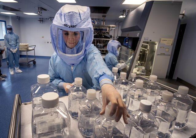 Dois funcionários de laboratório simulam o fluxo de trabalho em uma sala limpa da produção da vacina BioNTech Corona em Marburg, Alemanha, durante um dia de mídia no sábado, 27 de março de 2021.