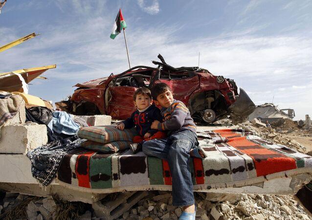 Filhos de uma família palestina descansam em meio aos escombros de sua casa destruída no leste de Jebaliya, norte da Faixa de Gaza, terça-feira, 27 de janeiro de 2009.