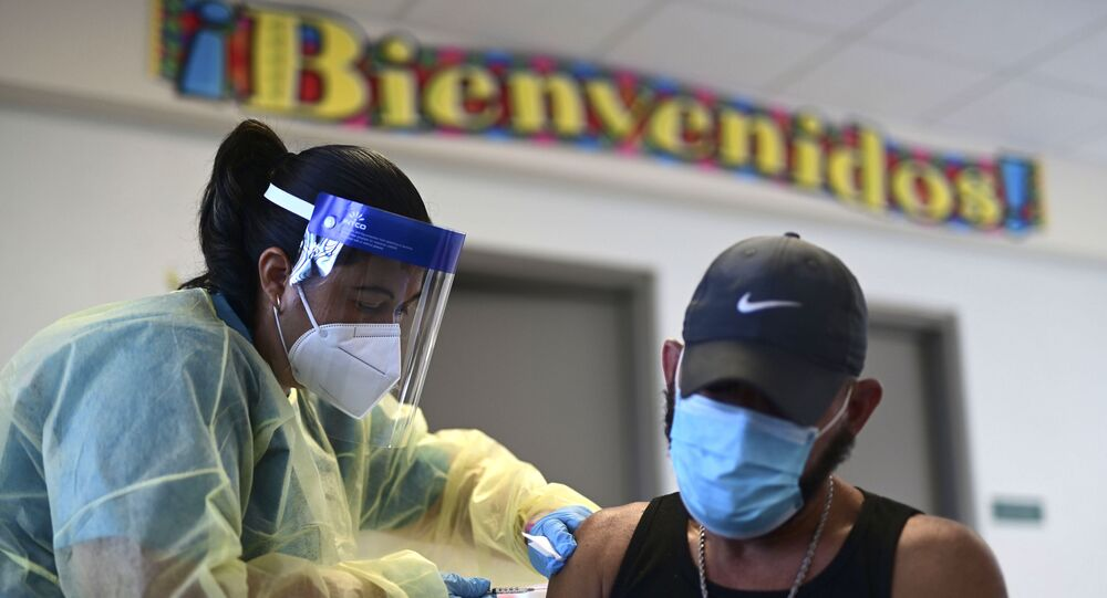 Em Vieques, Porto Rico, uma profissional de saúde aplica uma dose de uma vacina contra a COVID-19, em 10 de março de 2021