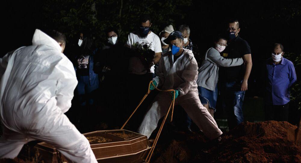 Em São Paulo, coveiros realizam o enterro noturno em meio à pandemia da COVID-19, em 7 de abril de 2021