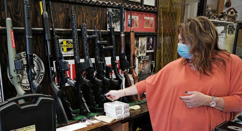 Vendedora mostra armas em loja especializada na Cidade de Jersey, no estado norte-americano de Nova Jersey, EUA, 25 de maio de 2021