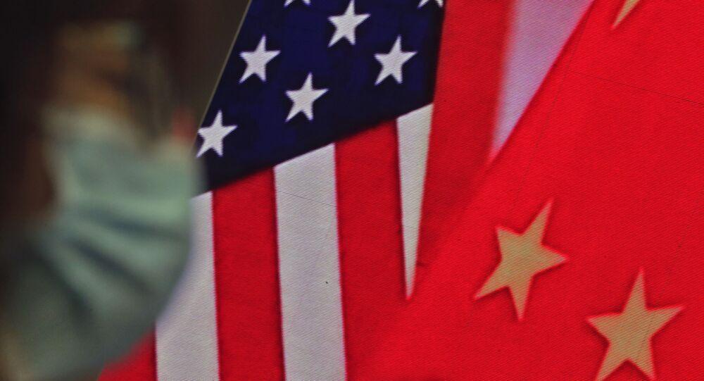 Mulher usando máscara sentada perto de uma tela que mostra bandeiras da China e dos EUA