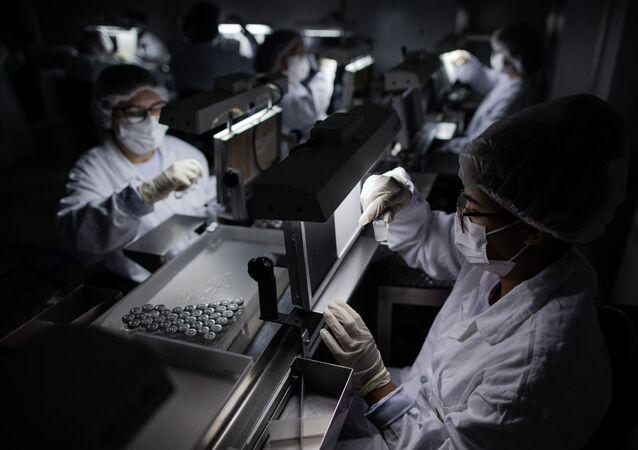 Funcionárias trabalham na inspeção visual da linha de produção da vacina CoronaVac, no Instituto Butantan, em São Paulo (SP).