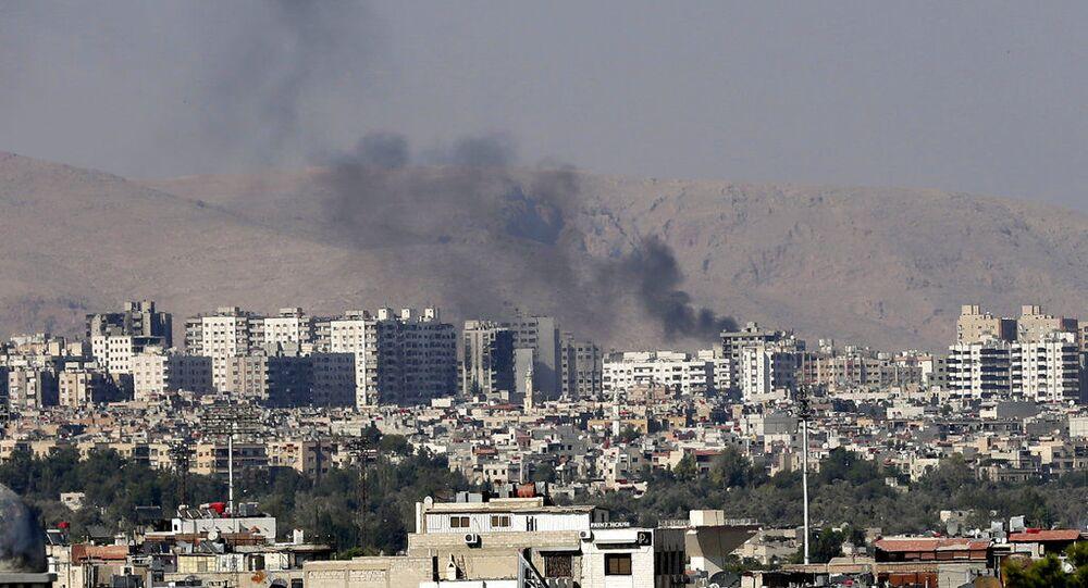 Colunas pretas de fumaça em um subúrbio de Damasco, Síria (foto de arquivo)