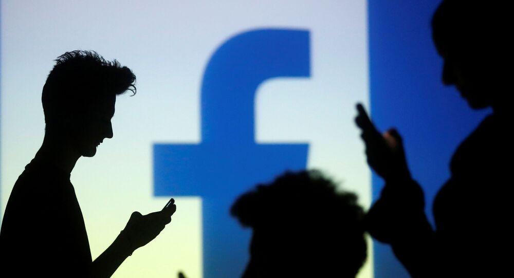 A silhueta de pessoas com dispositivos móveis em frente a uma tela projetada com um logotipo do Facebook, em ilustração de 29 de outubro de 2014