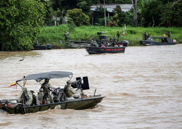 Um barco da marinha colombiana patrulha o rio Arauca enquanto um barco da marinha venezuelana permanece ancorado na fronteira entre a Colômbia e a Venezuela, visto de Arauquita, Colômbia, em 28 de março de 2021.