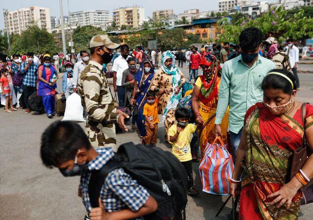 Pessoas usando máscaras protetoras caminham em fila em uma estação ferroviária em meio à disseminação da doença do coronavírus (COVID-19) em Mumbai, Índia, 9 de abril de 2021.