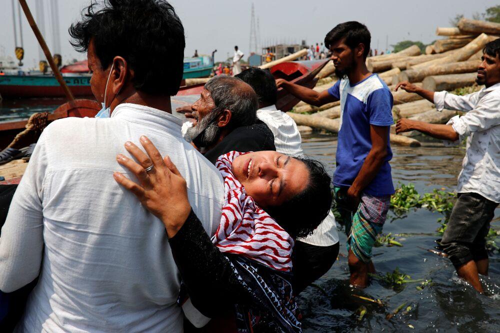 Pessoas enlutadas após balsa ter colidido com um cargueiro e afundado, Bangladesh, 5 de abril de 2021