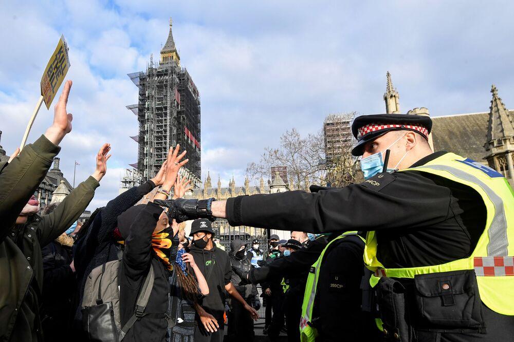 Manifestantes levantam suas mãos enquanto enfrentam policiais durante um protesto em Londres, Reino Unido, 3 de abril de 2021