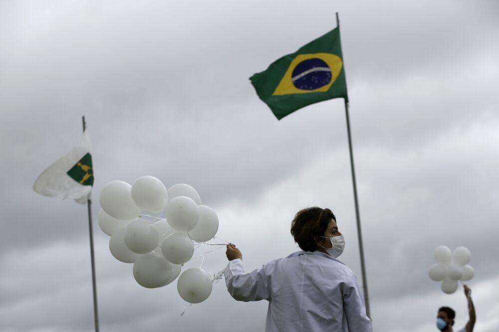 Enfermeira segurando balões em homenagem às vítimas da COVID-19 no Brasil, Brasília, 7 de abril de 2021.
