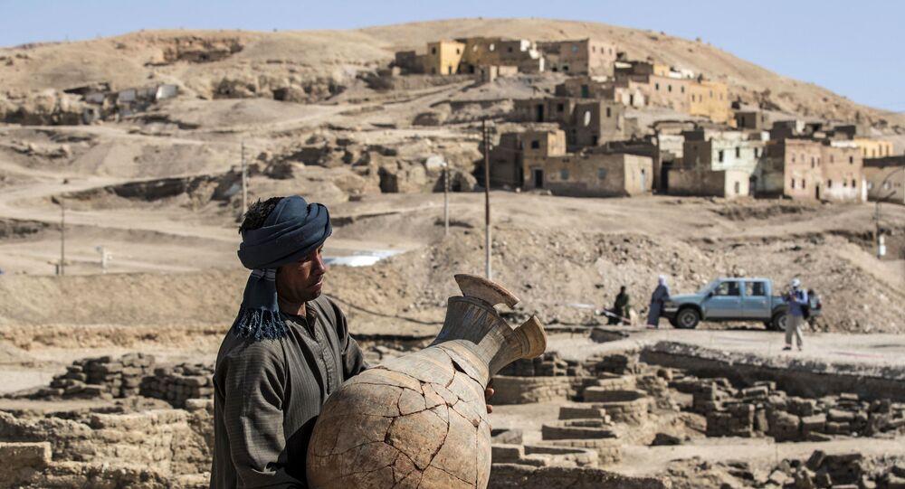 Operário carrega vaso no sítio arqueológico da cidade dourada desenterrada em Luxor, no Egito, 10 de abril de 2021