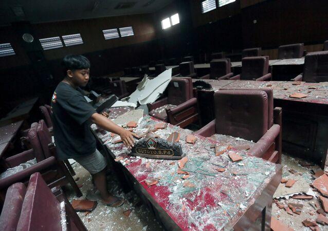 Em Blitar, na ilha de Java, na Indonésia, um homem limpa escombros após um terremoto atingir a ilha, em 10 de abril de 2021