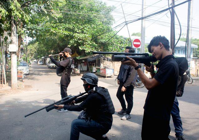 Manifestantes portando armas artesanais de ar comprimido durante protestos contra a junta militar na cidade de Rangum em Mianmar