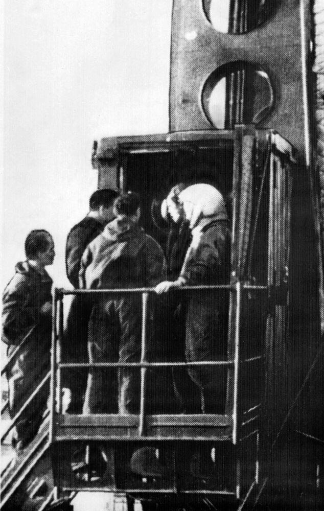 Cosmonauta soviético Yuri Gagarin rodeado por engenheiros entrando na espaçonave Vostok-1, 12 de abril de 1961