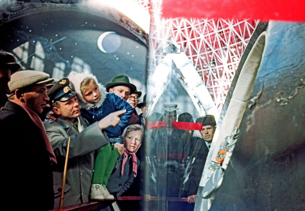 Cosmonauta Yuri Gagarin com sua filha Elena na exposição Engenharia Mecânica (Espaço) no Centro Panrusso de Exposições, Moscou, mostrando a espaçonave Vostok-1 em que voou ao espaço