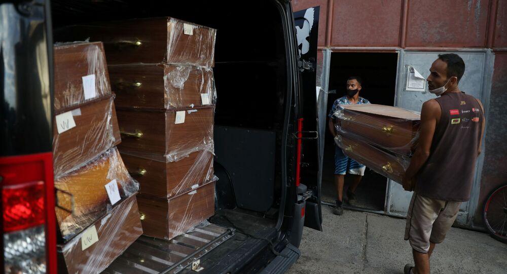 Trabalhadores carregam caixões para um carro funerário na cidade de Nova Iguaçu, Rio de Janeiro, 9 de abril de 2021