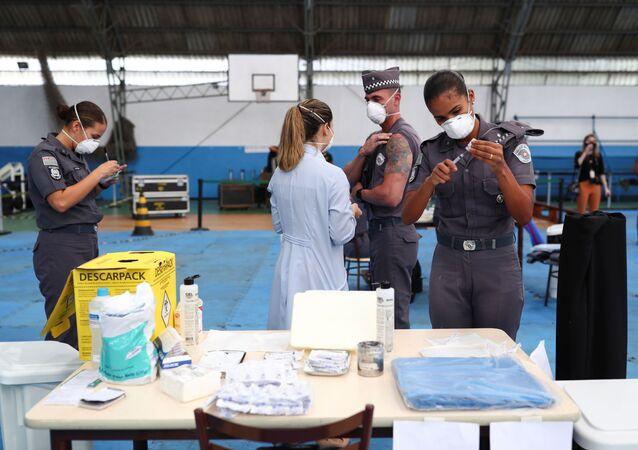 Profissional de saúde da polícia prepara uma dose da vacina da AstraZeneca contra a COVID-19 no primeiro dia de vacinação do governo estadual para policiais, São Paulo, Brasil, 5 de abril de 2021