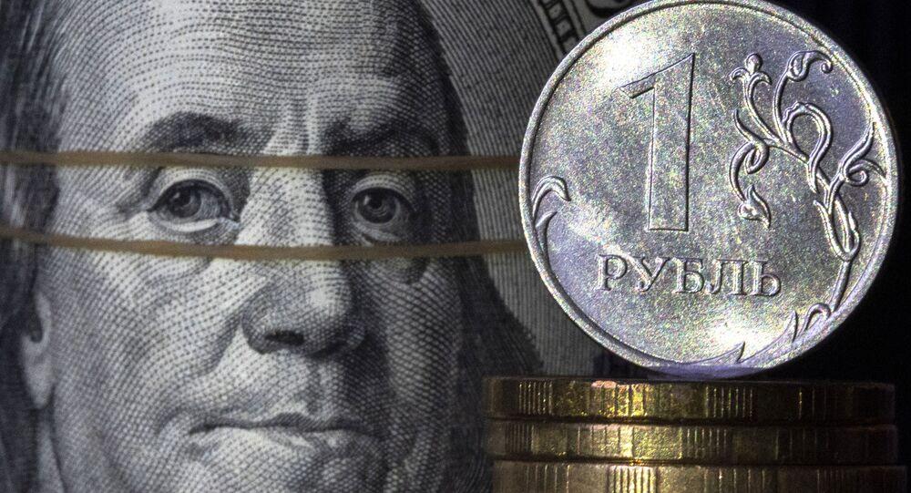Nota de dólar fotografada ao lado de moeda de um rublo, 7 de abril de 2021