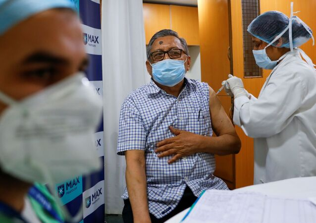 Em Nova Deli, na Índia, um homem recebe uma dose de vacina contra a COVID-19, em 17 de março de 2021