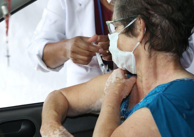 Idosa é vacina contra a COVID-19 em São Paulo.