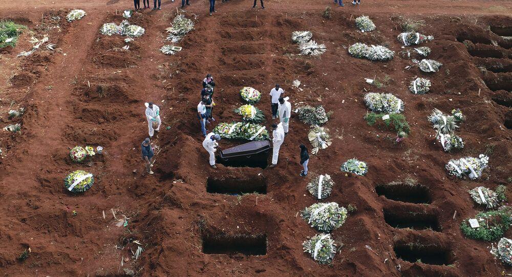 Agentes funerários usam roupa protetora durante enterro de vítima da COVID-19, no cemitério de Vila Formosa, São Paulo, 7 de abril de 2021
