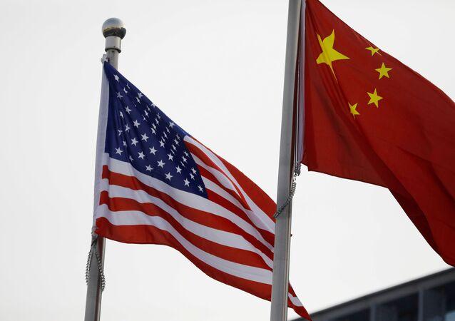 Bandeiras chinesas e americanas tremulam em frente ao prédio de uma empresa americana em Pequim, China, em 21 de janeiro de 2021.