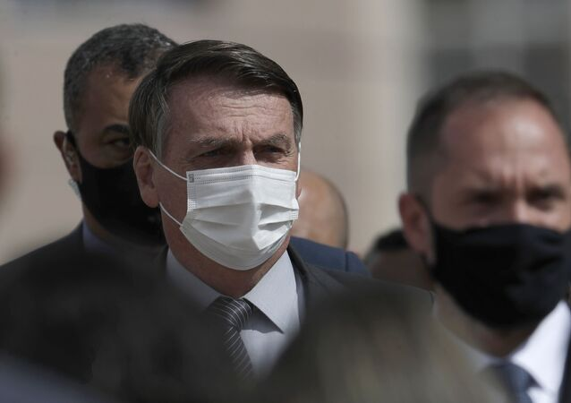 Presidente brasileiro, Jair Bolsonaro usando máscara facial durante sua chegada à cerimônia de entrega de casas construídas pelo governo em Brasília, 5 de abril de 2021