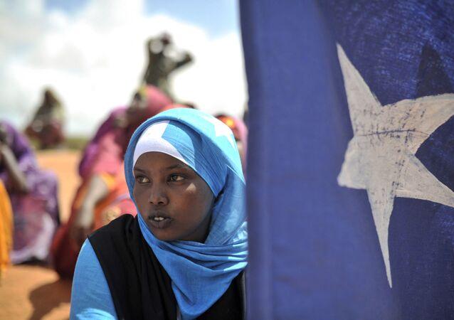 Jovem segura a bandeira da Somália enquanto participava de uma manifestação de uma milícia local, na cidade de Marka, Somália.