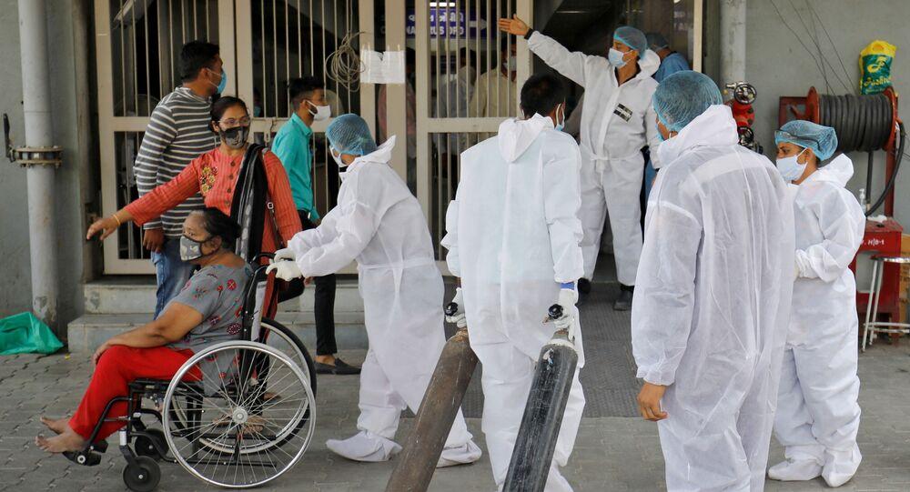 Funcionário de saúde carrega cilindros de oxigênio em um hospital para tratar casos da COVID-19 em Amedabade, Índia, 14 de abril de 2021