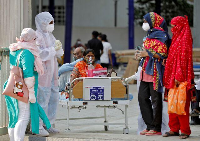 Em Ahmedabad, na Índia, uma paciente aguarda ser levada a um hospital em meio à pandemia da COVID-19, em 14 de abril de 2021