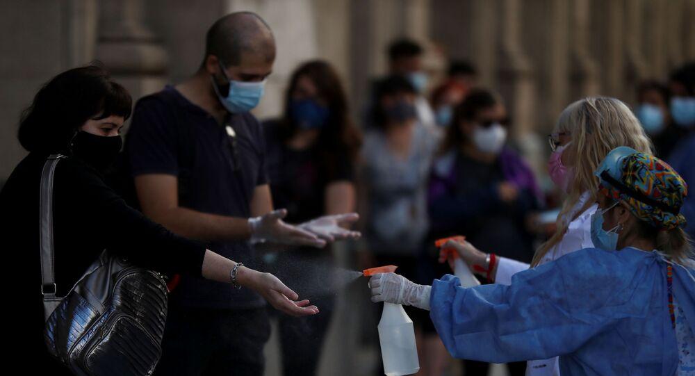 Em Buenos Aires, capital da Argentina, profissionais de saúde higienizam mãos de pessoas em fila para teste de detecção da COVID-19, em 13 de abril de 2021