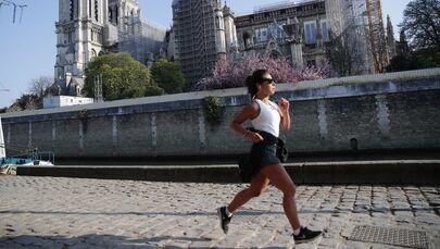 Mulher correndo em frente da catedral de Notre-Dame de Paris, França, 15 de abril de 2021