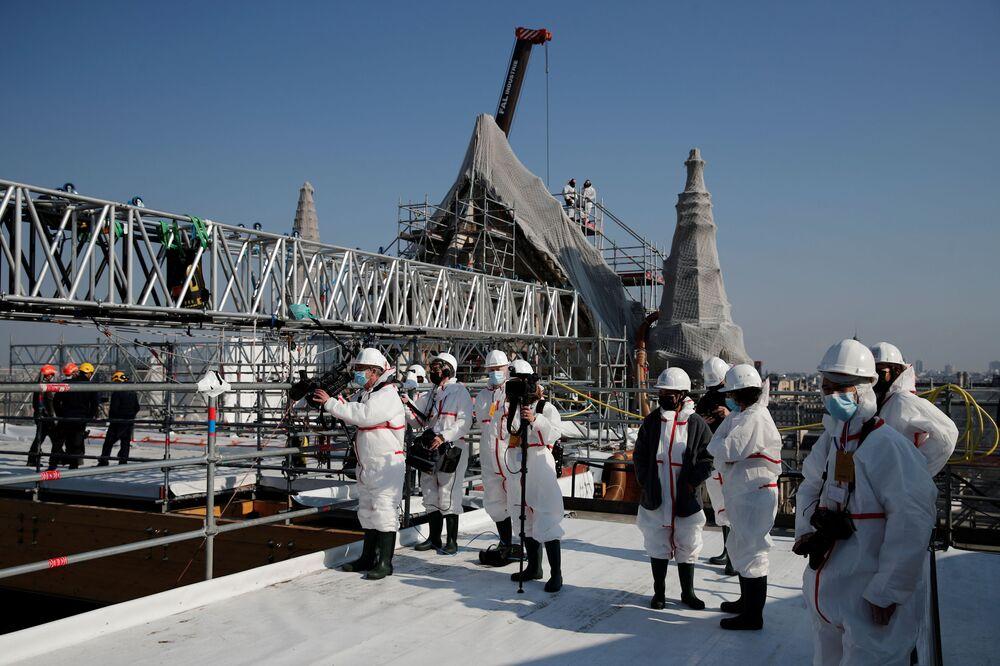 Jornalista trabalham no local de reconstrução do telhado de Notre-Dame, Paris, França, 15 de abril de 2021