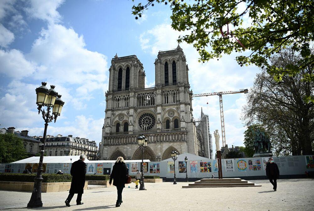 Pessoas caminham em frente da catedral de Norte-Dame, danificada por um incêndio há dois anos, Paris, França, 15 de abril de 2021