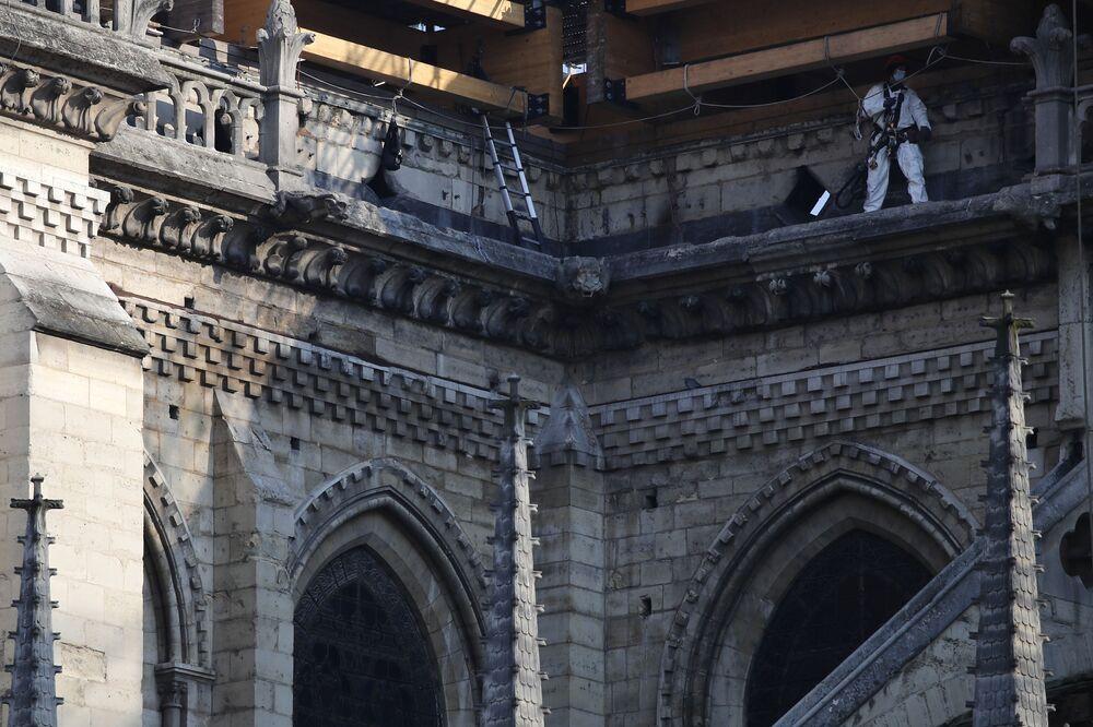 Operário caminha na cornija da catedral de Notre-Dame, Paris, França, 15 de abril de 2021