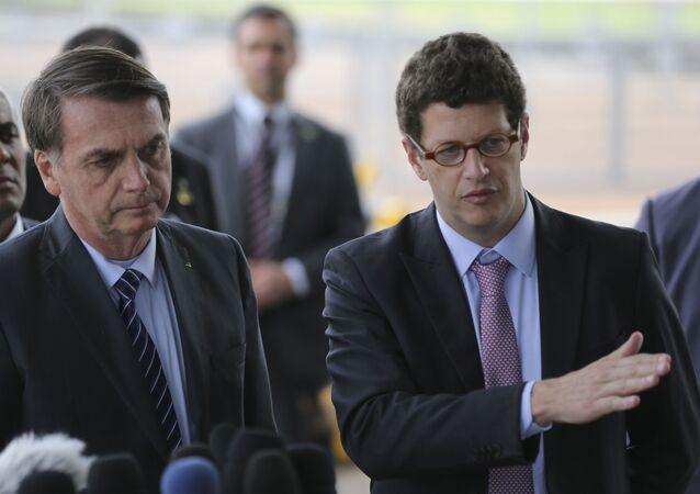 O presidente brasileiro, Jair Bolsonaro, e o ministro do Meio Ambiente, Ricardo Salles, recebem cumprimentos de simpatizantes na entrada do Palácio da Alvorada, em Brasília, em outubro de 2019