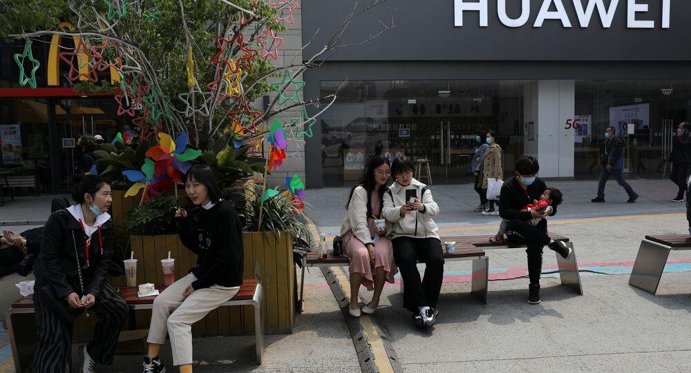 Pessoas descansam em frente a uma loja da Huawei em um shopping de Pequim, China, 15 de abril de 2021