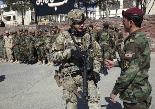 Soldado da Dinamarca, no centro à esquerda, fala com soldado recém-formado do Exército do Afeganistão na Academia Militar afegã em Cabul, Afeganistão, 24 de fevereiro de 2020