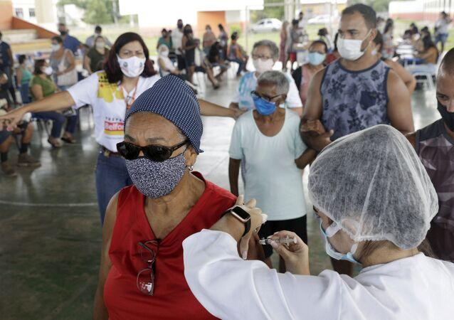Pessoas fazem fila para receber a vacina contra a COVID-19, em Belford Roxo, no Rio de Janeiro, no dia 31 de março de 2021