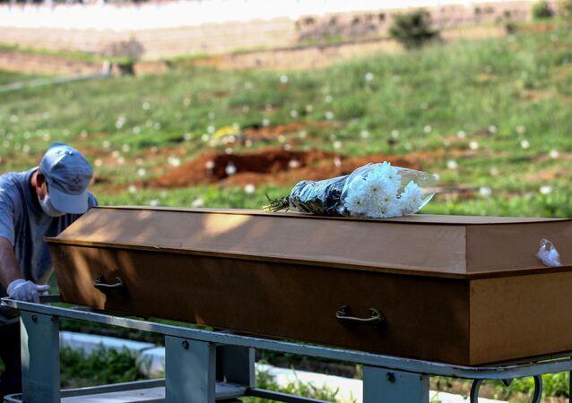 Funcionário empurra um caixão em sepultamento em cemitério na cidade de Porto Alegre, no Brasil, no dia 6 de abril de 2021