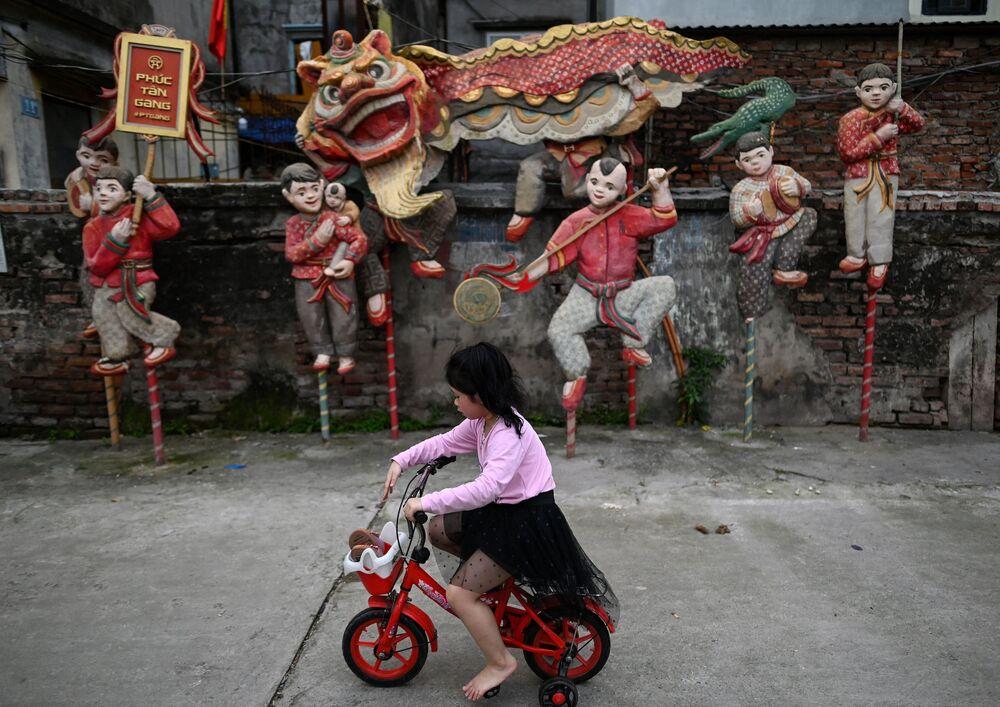 Menina passa de bicicleta ao lado da instalação Dança de Leão do artista Nguyen Xuan Lam, em Hanoi, 14 de abril de 2021