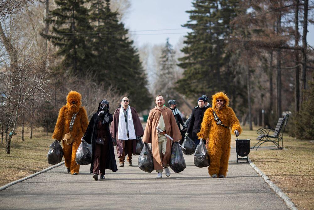 Voluntários fantasiados de personagens de Guerra nas Estrelas durante um evento de limpeza de ruas marcando o 60º aniversário do primeiro voo espacial tripulado, cidade de Irkutsk, Rússia, 12 de abril de 2021
