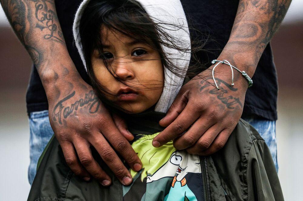Residente de Brooklyn com sua filha de três anos de idade durante protestos em frente ao Departamento de Polícia de Brooklyn, 13 de abril de 2021