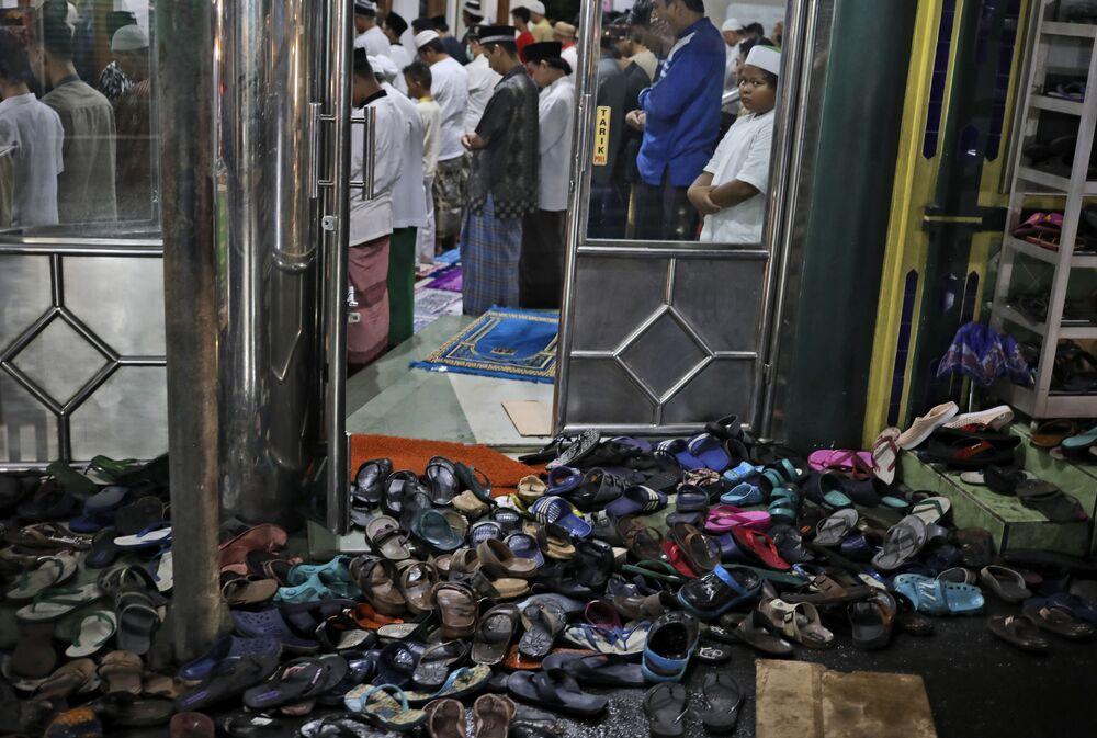 Sapatos deixados fora enquanto pessoas executam uma oração durante a primeira noite do mês sagrado do Ramadã na Indonésia, 12 de abril de 2021