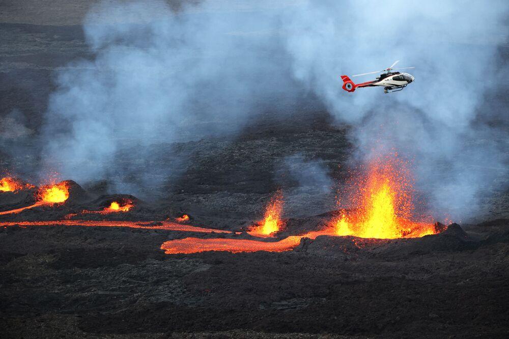 Helicóptero sobrevoa lava que corre do vulcão Piton de la Fournaise, na parte oriental da ilha de Reunião, departamento ultramarino da França, 10 de abril de 2021
